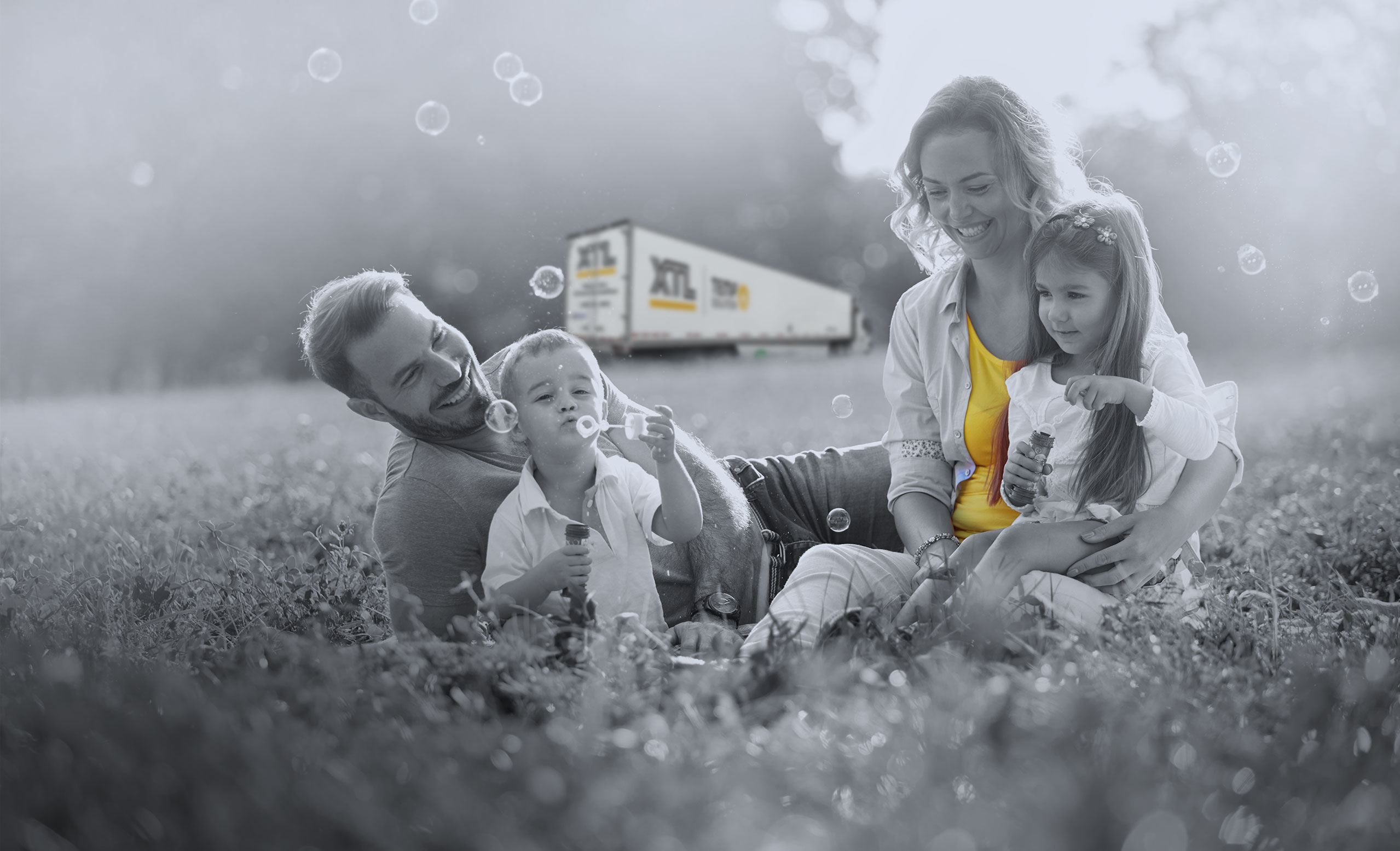 Family playing in the grass, blowing bubbles, with XTL transport truck in the background