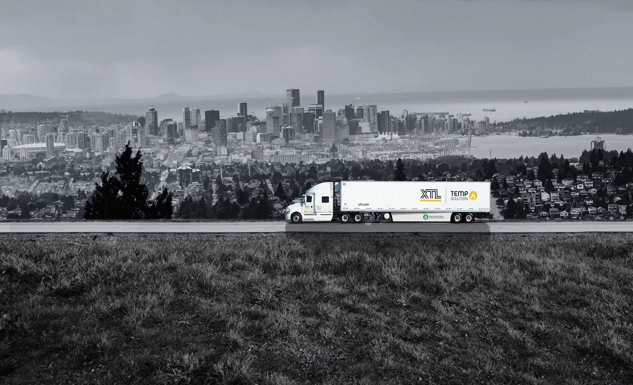XTL transport truck and trailer driving on road, with city of Vancouver in the background