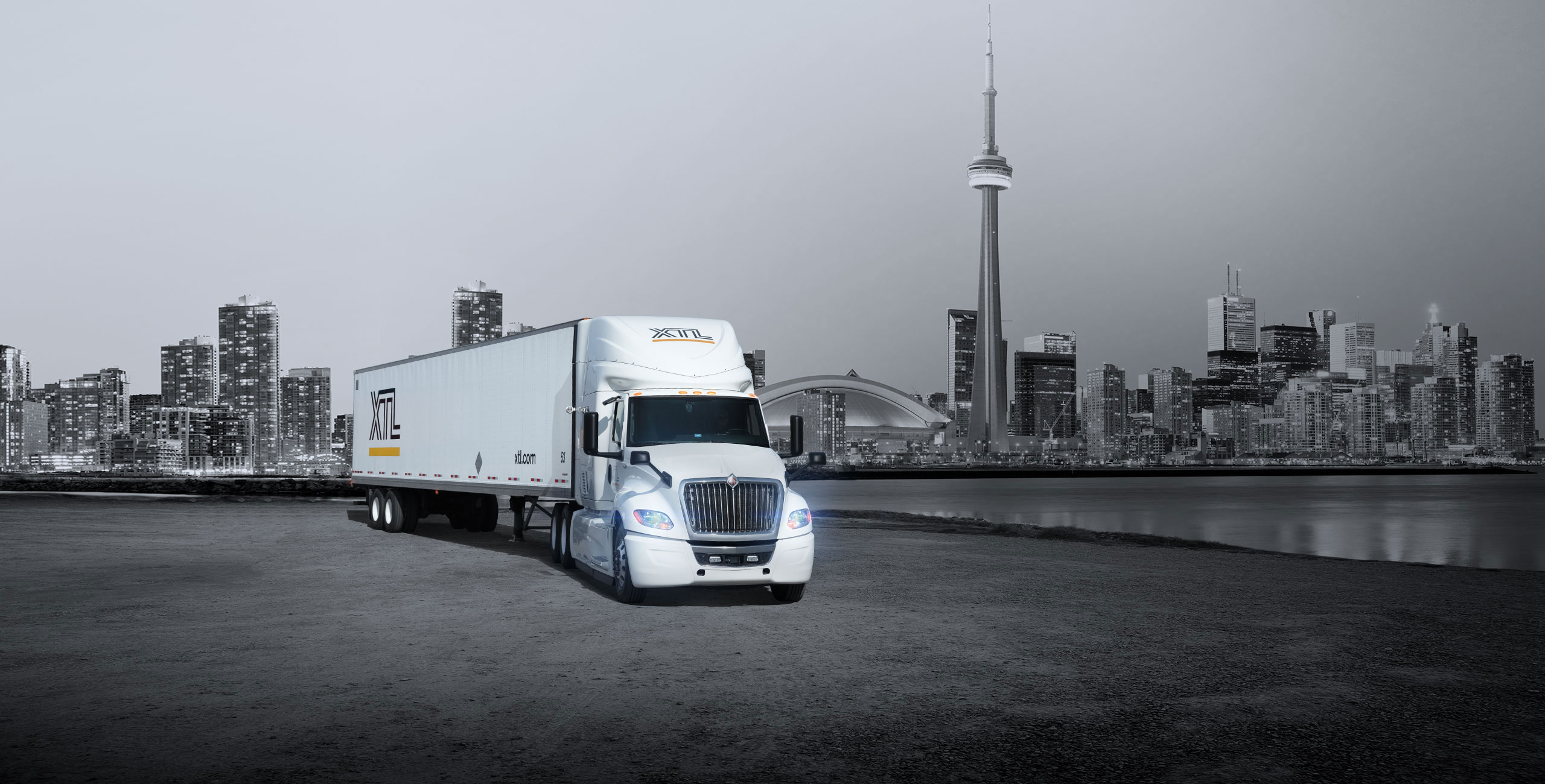 XTL transport truck parked, with city of Toronto in the background