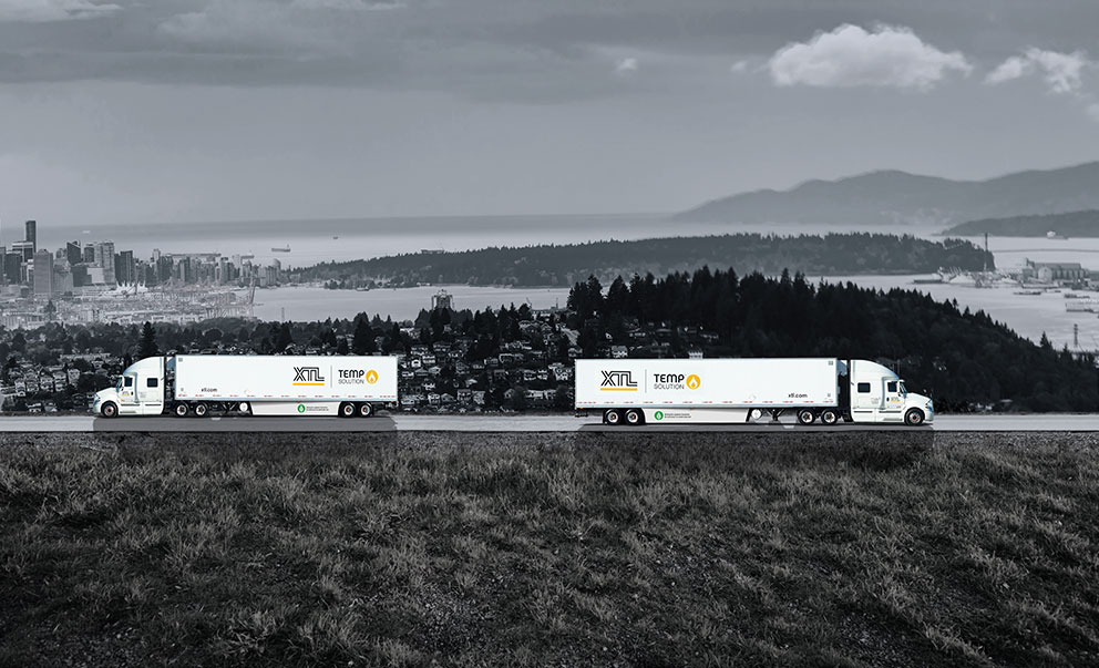 Two XTL transport trucks with trailers driving on the road with city of Vancouver in the background