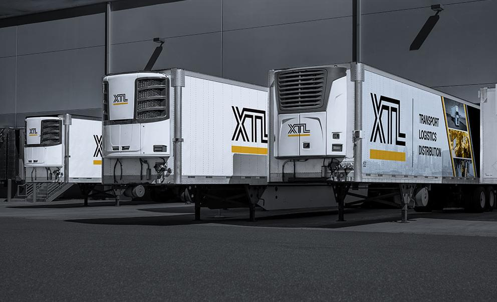 Multiple XTL refrigerated trailers backed into a crossdocking, warehouse facility